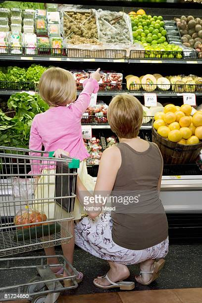 Woman in grocery store produce aisle with young girl pointing