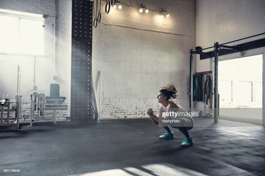 Woman in gym doing squats : Stock Photo