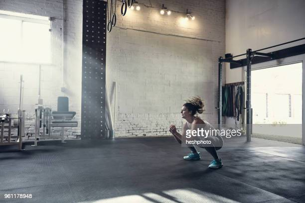 woman in gym doing squats - hurken stockfoto's en -beelden