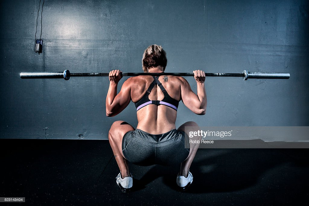 Woman in gym gym with weight bar on shoulders : Stock Photo