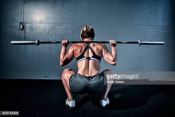 woman in gym gym with weight bar on shoulders - robb reece stock pictures, royalty-free photos & images