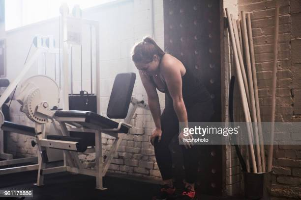 woman in gym, hands on knees exhausted - heshphoto stock pictures, royalty-free photos & images
