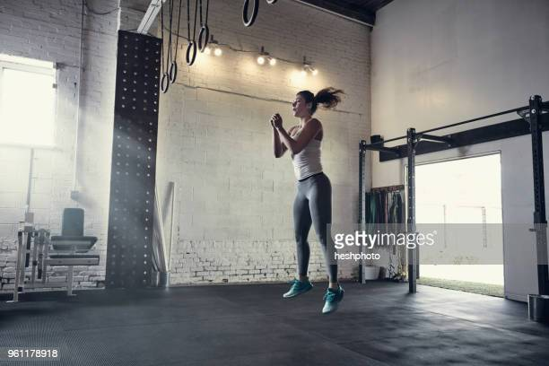 woman in gym jumping in mid air - heshphoto stock pictures, royalty-free photos & images