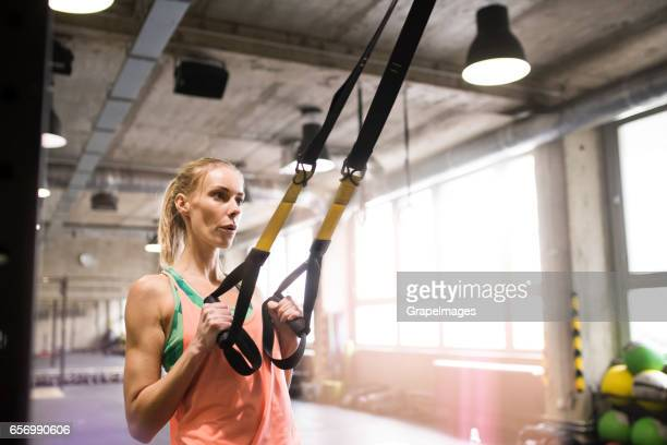 woman in gym training arms with trx fitness strips - strap stock photos and pictures