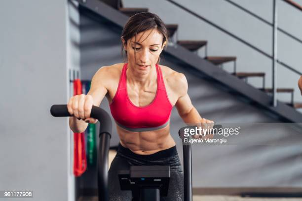 woman in gym using exercise bike - exercise bike stock photos and pictures