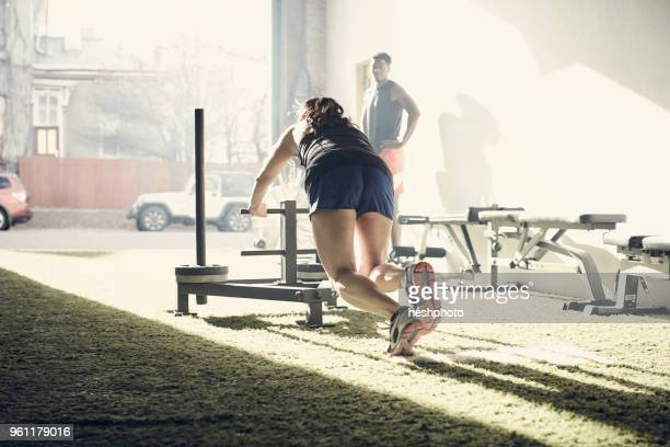 woman in gym using exercise equipment - heshphoto stockfoto's en -beelden