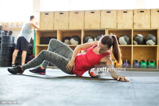 Woman in gym using support roller