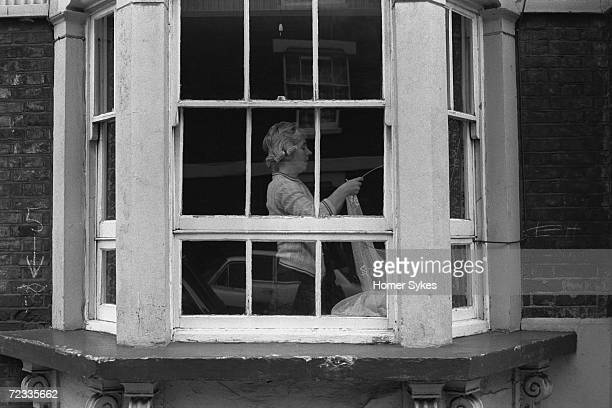 A woman in hair curlers puts up lace curtains in her ground floor flat in Whitechapel to prevent people from looking in 1975
