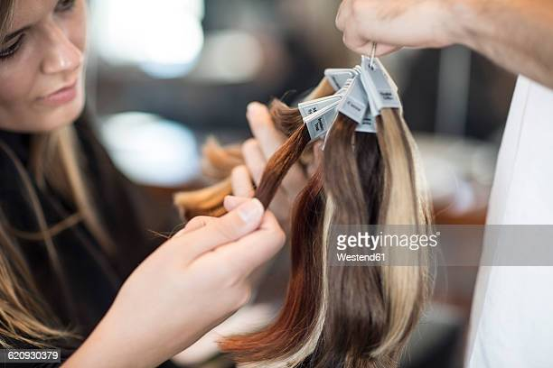 Woman in hair salon chooing new hair color