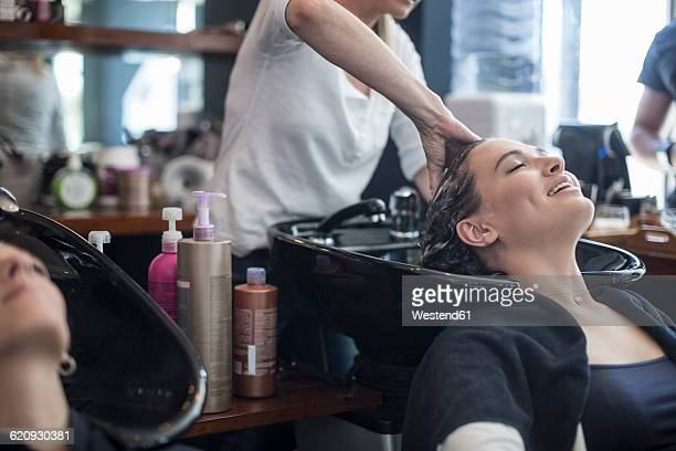 Woman in hair salon getting hair washed