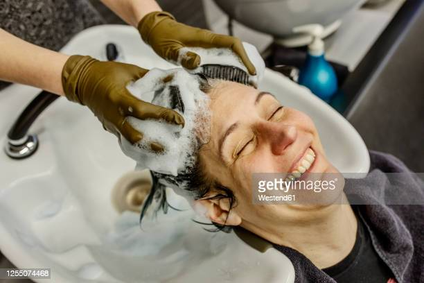 woman in hair salon getting hair washed with brushes - washing hair stock pictures, royalty-free photos & images