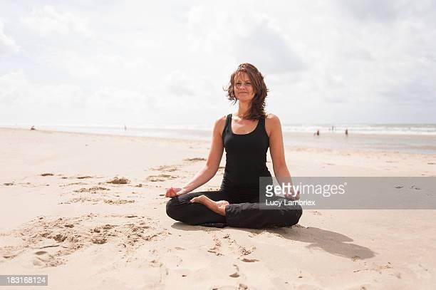Woman in half lotus on the beach