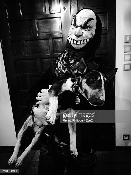 woman in halloween mask carrying bull terrier at home - magic doors stock pictures, royalty-free photos & images