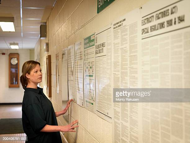 woman in hallway looking at notices on wall - monty rakusen stock pictures, royalty-free photos & images