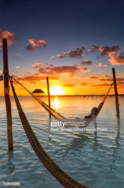 Woman in hammock at sunset, Holbox Island, Cancun, Yucatan, Mexico
