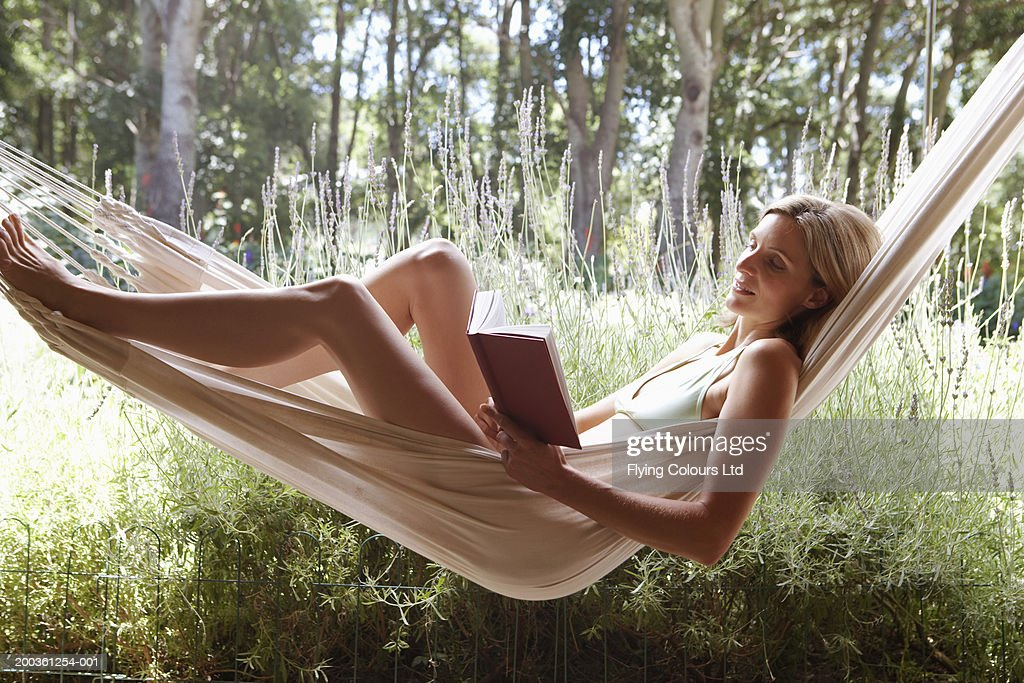 Woman in hammock reading book, side view : Stock Photo