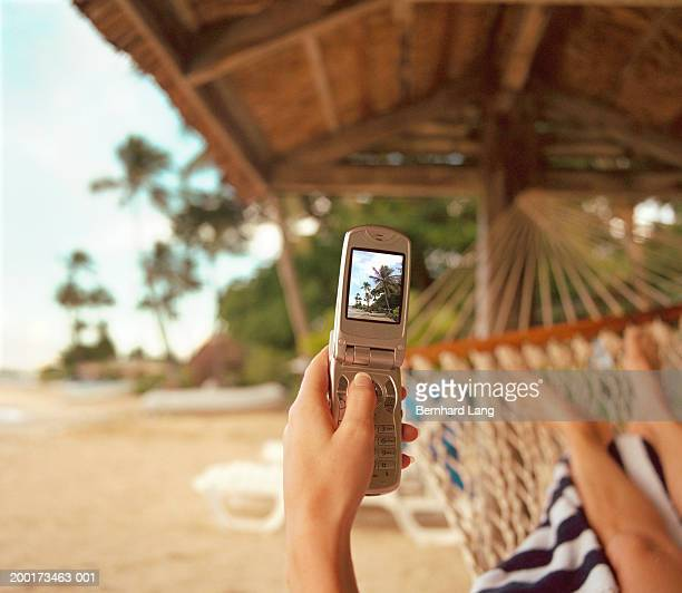 Woman in hammock taking photo of beach with  mobile phone camera