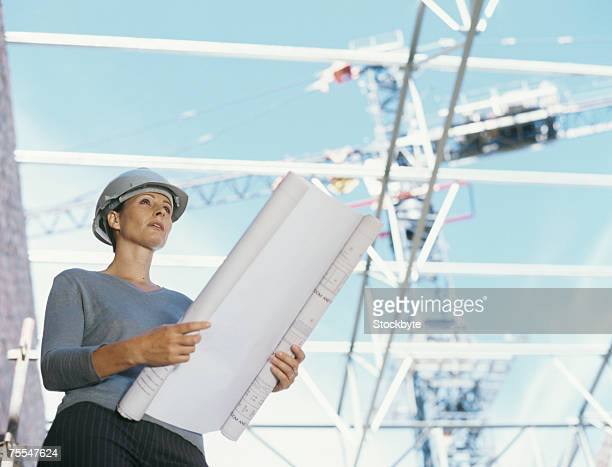 Woman in hard hat looking at blueprints on construction site,low angle view