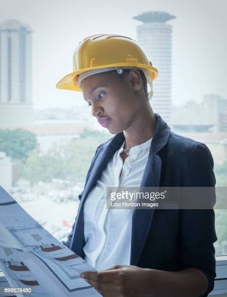 woman in hard hat looking at building plans - nairobi stock pictures, royalty-free photos & images