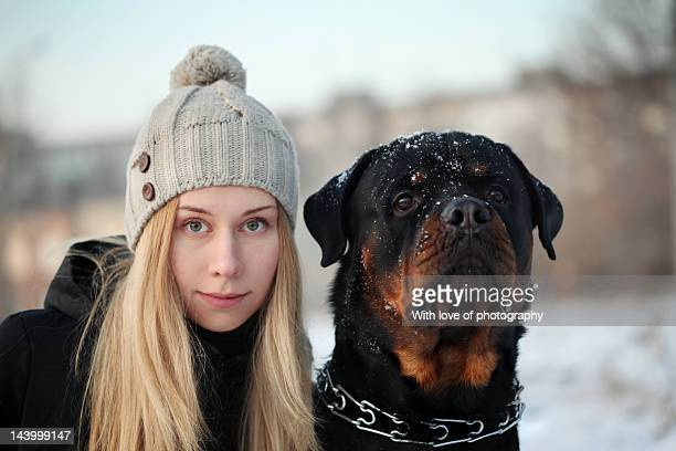 Woman in hat and rottweiler dog in winter