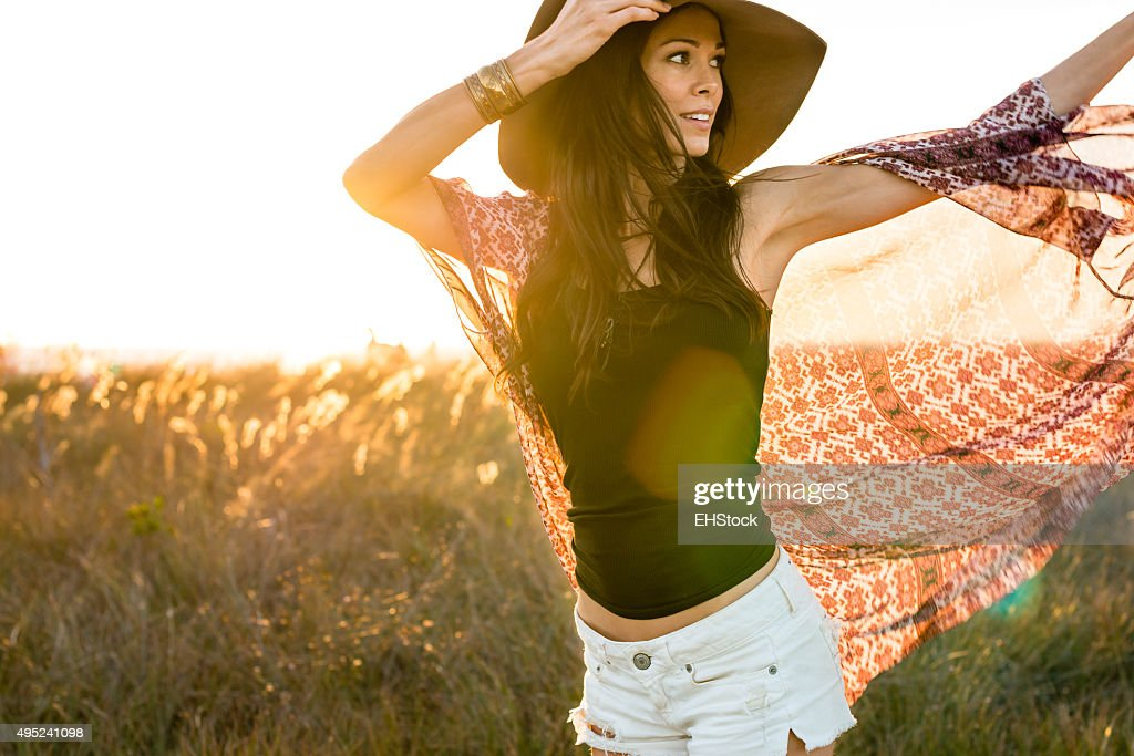 Woman in hat running through field : Stock Photo