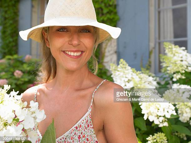 woman in hat standing in garden, smiling, close-up, portrait - saint ferme stock pictures, royalty-free photos & images