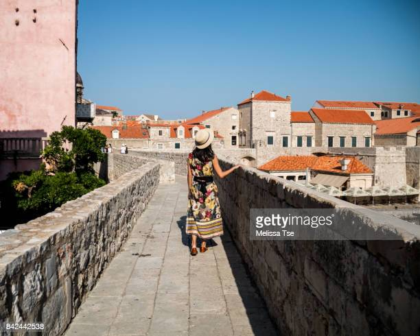 Woman in Hat Walking Along a Section of the Walls of Dubrovnik