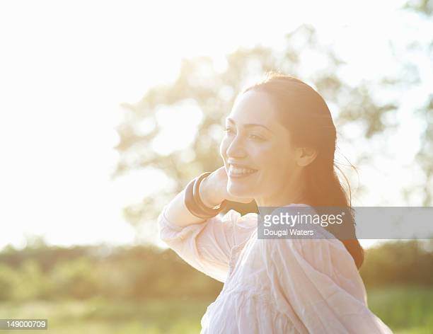 Woman in hazy Summer meadow smiling.