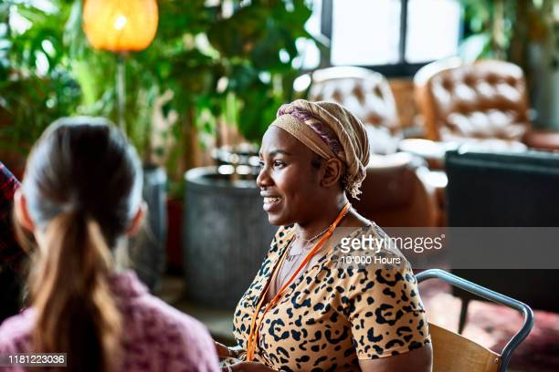 woman in headdress talking to friends in cafe - mid adult women stock pictures, royalty-free photos & images
