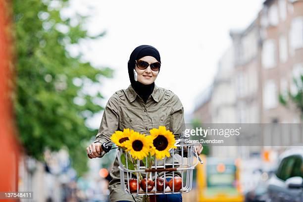 Woman in headscarf biking on cell phone
