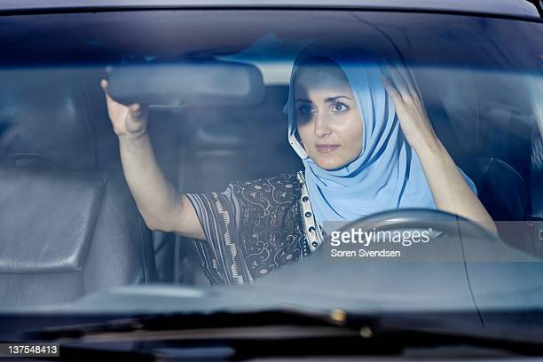 Woman in headscarf checking mirror