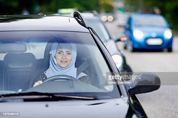Woman in headscarf driving on cell phone