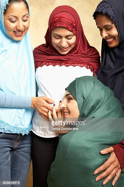 Woman in headscarf listening to friend's pregnant belly