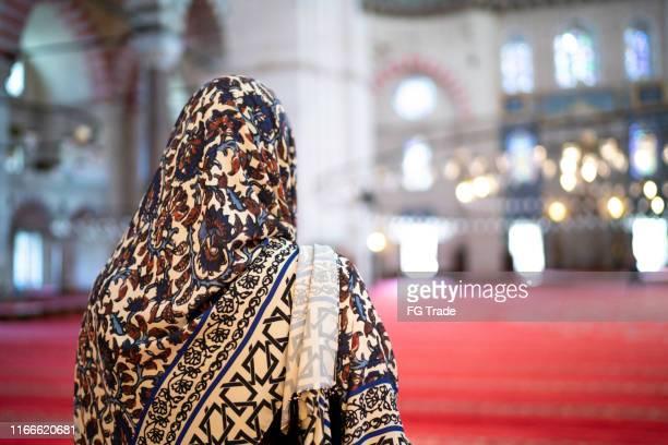 vrouw in hoofddoek bidden in een moskee, istambul, turkije - godsdienstige gebouwen stockfoto's en -beelden
