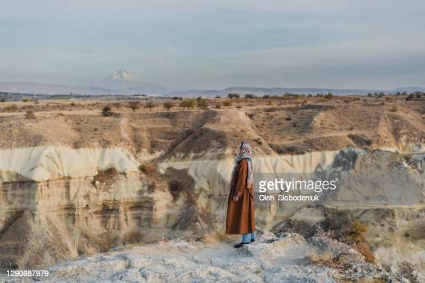 トルコのカッパドキアの洞窟に立って見ているヘッドスカーフの女性 - アナトリア ストックフォトと画像
