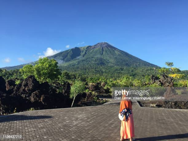 Woman In Headscarf Standing On Footpath Against Mountain