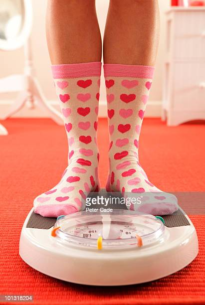 woman in heart socks weighing in on a scales  - human leg stock pictures, royalty-free photos & images