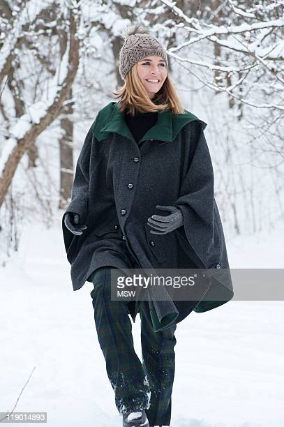 woman in heavy cape walking in snow - cape garment stock photos and pictures