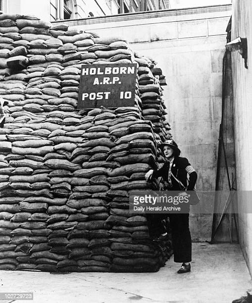 Woman in helmet standing beside stack of sandbags 14 September 1939 The well sandbagged ARP post and public shelter in London' A sign on the sanbags...