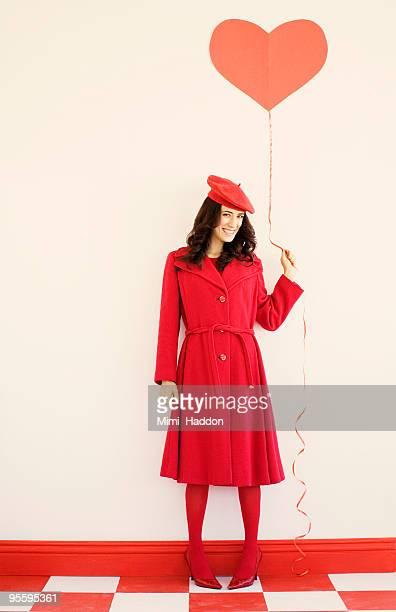 woman in her 20's holding heart balloon - ベレー帽 ストックフォトと画像