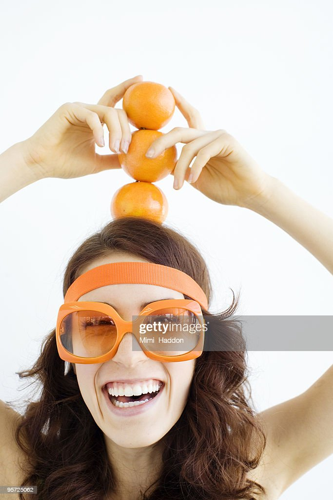 Woman in her 20's Holding Stack of Oranges on Head : Stock Photo