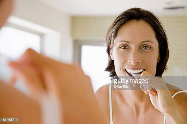 A woman in her 40s brushing her teeth.