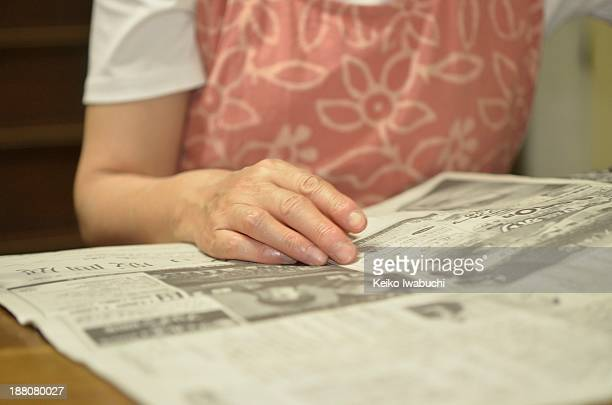 Woman in her 60's reading a newspaper