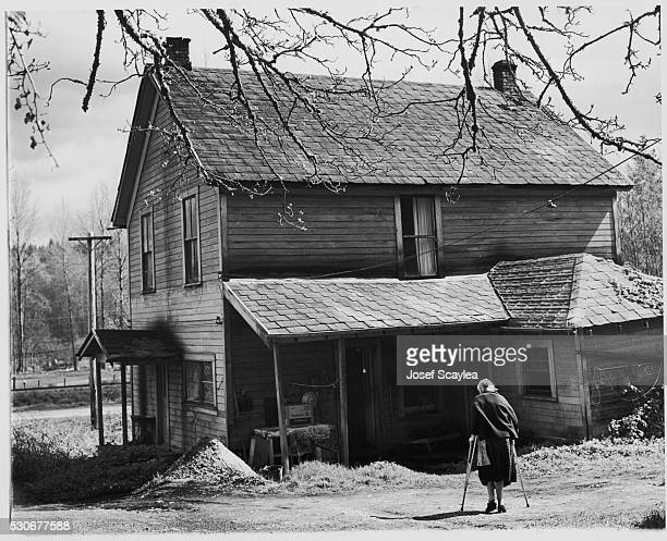 A woman in her 90s walks with crutches in the yard in front of her home