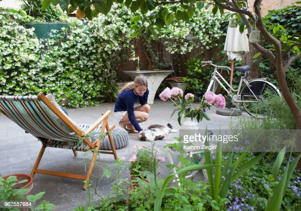 woman in her backyard, squatting down to play with her cat - jardin fleuri photos et images de collection