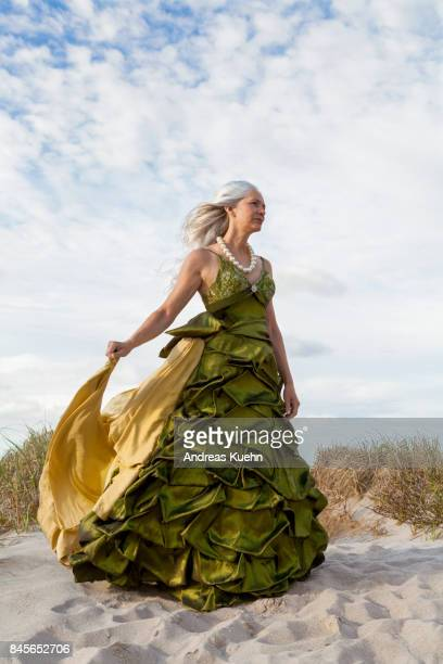 woman in her late fifties with long, silvery, grey hair blowing in the wind wearing an evening gown at the beach. - evening gown stock pictures, royalty-free photos & images