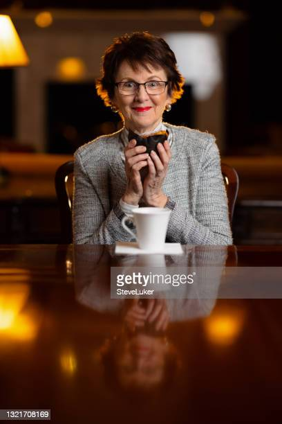 woman in her living room about to eat a muffin and drink coffee - coffee drink stock pictures, royalty-free photos & images