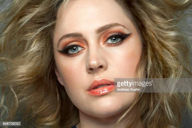 Woman in her mid thirties wearing lipstick and make up with big, wavy, tousled, blond hair, close up.