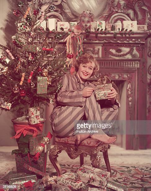 A woman in her pyjamas sits under a christmas tree opening presents