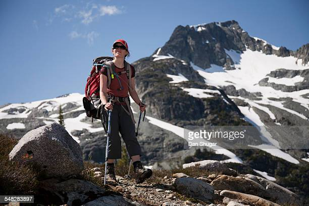 a woman in her thirties hikes in the alpine region of semaphore lakes, with face mountain in the background. - semaphore stock pictures, royalty-free photos & images